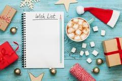 Kopp av varm kakao eller choklad med marshmallowen, feriegarneringar och anteckningsbok med önskelistan, planera för jul Arkivbilder