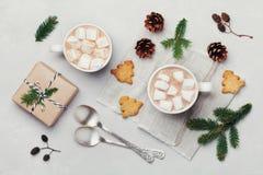 Kopp av varm kakao eller choklad med marshmallowen, kakor och julgåvan på den vita tabellen från över Traditionell vinterdrink Arkivbilder