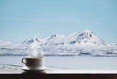 Kopp av varma drinkar med ånga på träskrivbordet och den härliga vinterlandskapsikten i morgonen Royaltyfri Fotografi
