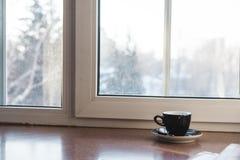 Kopp av varma drinkar på den wood tabellen, med det vita fönstret och solljus i morgonen Arkivfoton