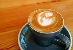Kopp av varmt cappuccinokaffe med Lattekonst i Grey Cup Served på trätabellen royaltyfri foto