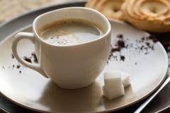 Kopp av varmt espressokaffe och kakan Arkivbild