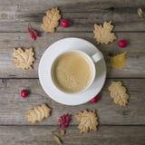 Kopp av varmt kaffe, kakor i formsidor, torra höstsidor, hagtorn och barberryfrukter på en träbakgrund Bästa sikt, lägenhet fotografering för bildbyråer