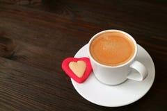 Kopp av varmt kaffe med en hjärta formad kaka på den mörka bruna trätabellen royaltyfria bilder