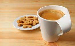 Kopp av varmt kaffe med en platta av kakor på trätabellen royaltyfri foto