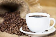 Kopp av varmt kaffe med kaffebönor Royaltyfria Bilder