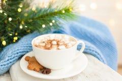 Kopp av varmt kaffe med mannen och marshmallower för julpepparkakakaka arkivbild