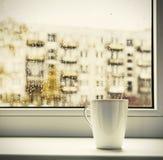 Kopp av varmt kaffe på fönstret Royaltyfria Foton