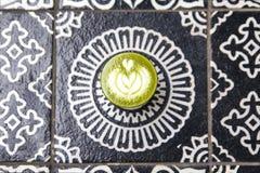 Kopp av varmt matchacappucinokaffe på konstbakgrundsgolv Royaltyfria Bilder