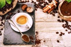 Kopp av varmt svart kaffe i inställning med grillade kaffebönor royaltyfria bilder
