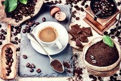 Kopp av varmt svart kaffe i inställning med grillade kaffebönor royaltyfria foton