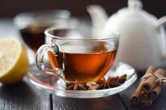 Kopp av varmt svart te med citronen och kryddor i den glass koppen på svart Arkivfoton