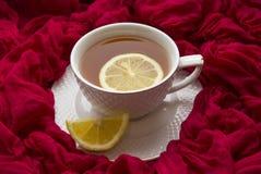 Kopp av varmt te med citronen och en röd halsduk arkivbild
