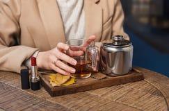 Kopp av varmt te och röd läppstift panera royaltyfri fotografi