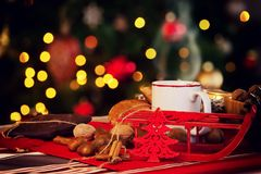 Kopp av varmt te på med det behind julträdet Arkivfoton
