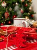 Kopp av varmt te på med det behind julträdet Arkivfoto