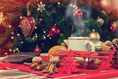 Kopp av varmt te på med det behind julträdet Royaltyfria Foton