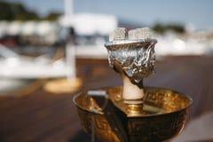Kopp av vattenpipan med brinnande kol på bakgrunden av vita yachter royaltyfri foto