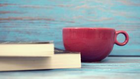 Kopp & bok för kaffe röd på trätabellen Arkivfoto