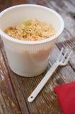 Kopp-en-nudlar pastaramen i plast- kopp på den wood tabellen Royaltyfria Foton
