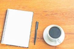 Kopp för anteckningsbok och för vitt kaffe för svartpenna på wood tabellbakgrund Royaltyfri Foto