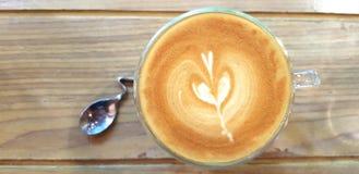 Kopp för bästa sikt av varmt konstlattekaffe och exponeringsglas av vatten med den härliga designskeden på trätabellen eller bakg Royaltyfria Foton