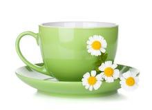 Kopp för grönt te med kamomillar Arkivfoto
