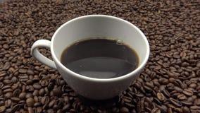 kopp för 4k A av svart kaffe över grillade kaffebönor Ingrediens för kaffe arkivfilmer