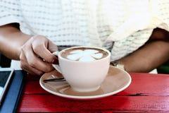 Kopp för kaffe för kvinnahandhandtag i coffee shop Royaltyfri Foto
