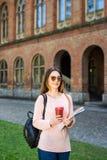 Kopp för kaffe för lyckligt studentinnehavtagande bort utomhus royaltyfria bilder
