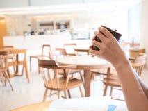Kopp för kaffe för kvinnahandhåll varm i emply kafé Arkivbild