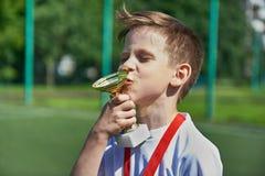 Kopp för kyssar för vinnarepojkefotbollsspelare Arkivfoto