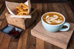 Kopp för Lattekonstkaffe med mellanmålet arkivfoto