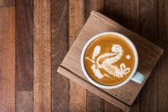 Kopp för Lattekonstkaffe på träplattan arkivfoto