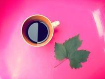 Kopp för svart kaffe på rosa bakgrund Arkivfoto