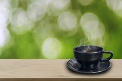 Kopp för svart kaffe på trä Fotografering för Bildbyråer