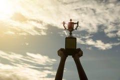 Kopp för trofé för vinnare för konturhand hållande i en mästerskap arkivbilder