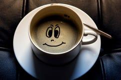 Kopp för vitt kaffe med den roliga framsidan arkivfoto