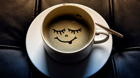 Kopp för vitt kaffe med den roliga framsidan royaltyfri bild