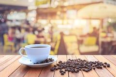 Kopp för vitt kaffe och kaffebönor på den wood tabellen med suddig bac Arkivfoton