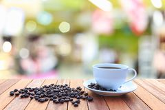 Kopp för vitt kaffe och kaffebönor på den wood tabellen med suddig bac Arkivbild