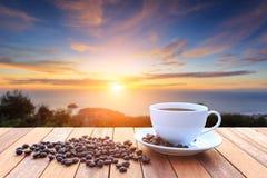 Kopp för vitt kaffe och kaffebönor på den wood tabellen och sikt av solar Arkivbilder