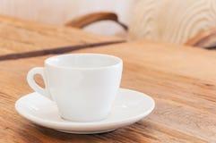 Kopp för vitt kaffe på den wood tabellen Royaltyfri Bild