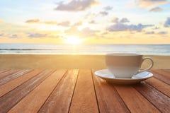 Kopp för vitt kaffe på den wood tabellen och sikt av solnedgången eller soluppgångbac Arkivbilder