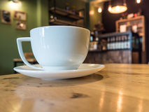 kopp för vitt kaffe på det wood skrivbordet i kafécoffee shop Royaltyfri Bild