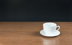 Kopp för vitt kaffe på en tabell med svart bakgrund Arkivbild