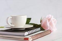Kopp för vitt kaffe på spiralanteckningsböcker med den söta rosa färgrosblomman royaltyfri foto