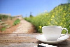 Kopp för vitt kaffe på träskrivbordutrymmeplattformen på lantgård av fältet Royaltyfria Bilder