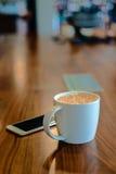 Kopp för vitt kaffe på trätabellen på coffee shop Arkivfoto