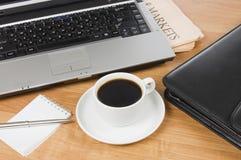 Kopp från kaffe på bärbar dator på tabellen royaltyfria bilder